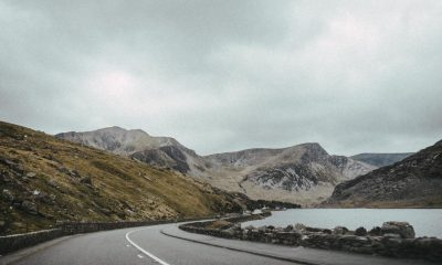 landscape photography of road near mountain under cloudy sky